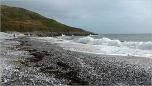 View looking east across the water's edge at Pwll Du Bay