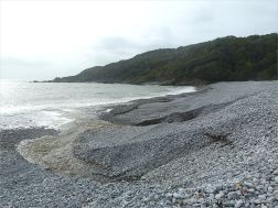 Two streams of water running from the base of shingle banks into the sea