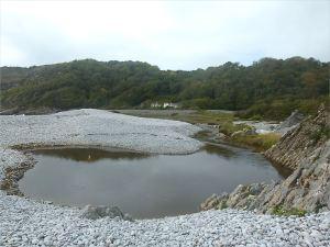 Water dammed behind the shingle banks at Pwll Du Bay