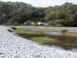 The water of the Bishopston Pill watercourse dammed up behind the shingle banks at Pwll Du