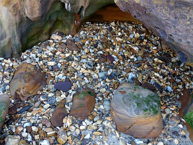 Flint pebbles and boulders on the north side of Redend Point at Studland Bay in Dorset, England.