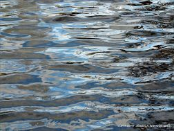 Natural water reflection patterns and textures in the rippled surface of a fountain bowl