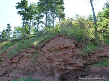 Low cliff of red Permian rock on the shore at Lord Selkirk Provincial Park in Prince Edward Island