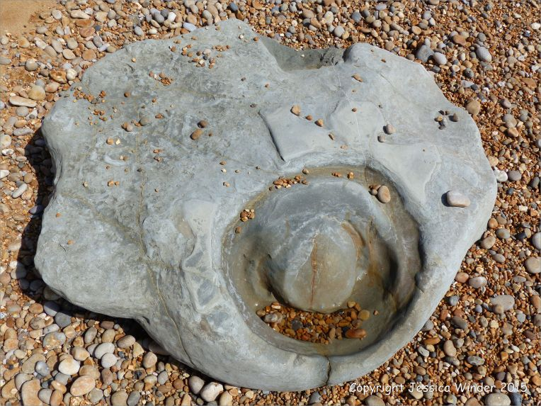 Beach boulder in shingle at the water's edge
