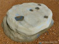 Beach boulder on wet shingle at the beach