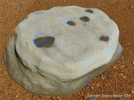 Beach boulder on wet shingle at the beach
