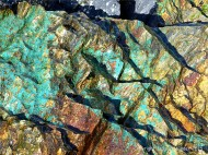 Blue-green copper minerals in cliff rocks at Porth Kidney in Cornwall, England