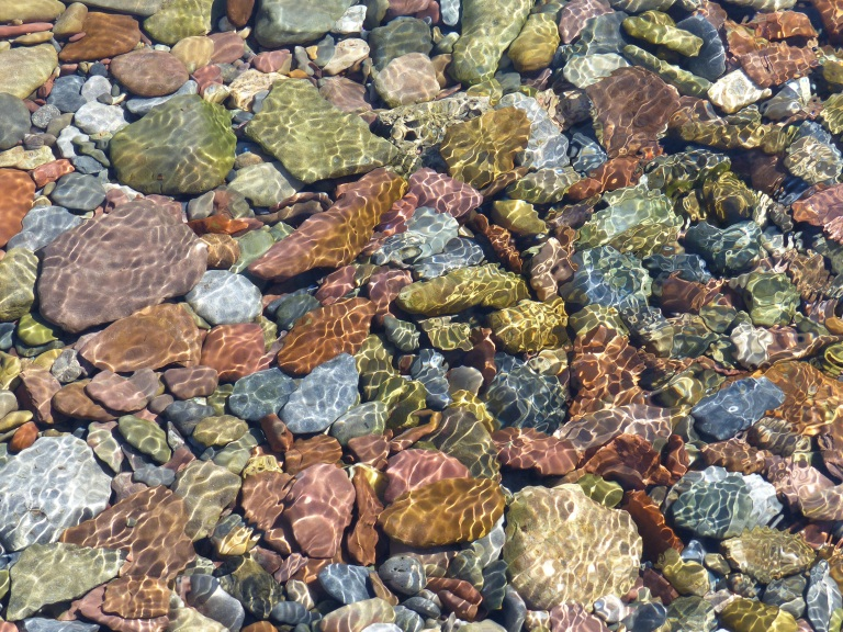 Coloured pebbles under water on a sunny day