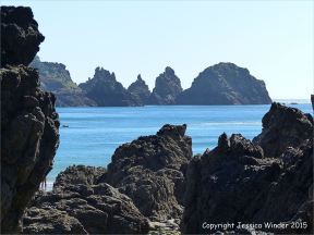 View across the rocky beach outcrops at Moulin Huet Bay towards the Pea Stacks