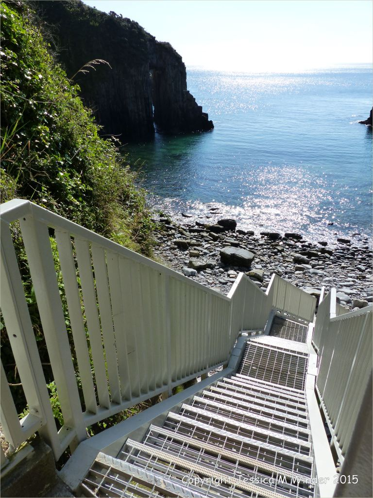 Metal steps leading down to Church Doors, the middle Cove at Skrinkle Haven on the South Pembrokeshire Coast in Wales