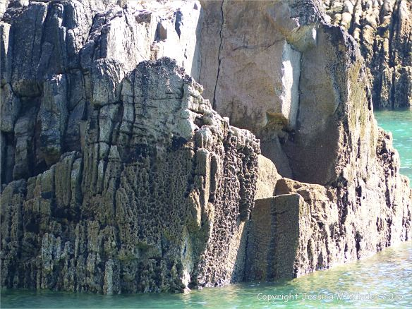Carboniferous Black Rock Limestone with bioerosion on the waterline around the natural Horseback arch on the seashore at Church Doors on the South Pembrokeshire Coast in Wales