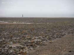 View looking towards the lighthouse at Whiteford on the Gower Peninsula showing rock strewn beach