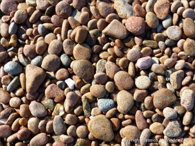 Colourful and patterned pebbles of igneous rocks