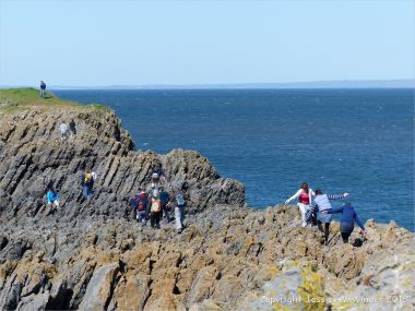 People clambering over rocks at Low Neck on Worm's Head