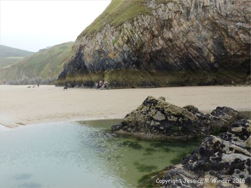 Tide pool and wet sand at low tide on Rhossili beach
