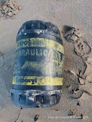 Black plastic oil drum washed ashore