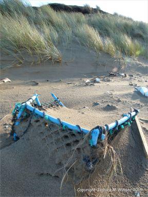 Blue plastic crate flotsam on sandy beach
