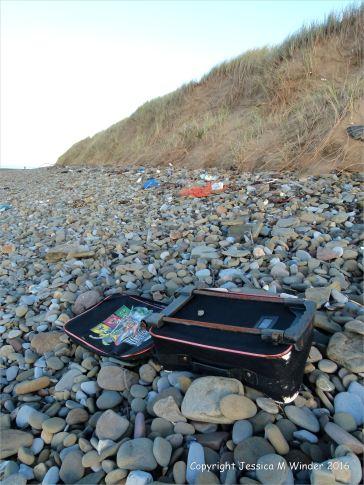 Flotsam suitcase on beach pebbles