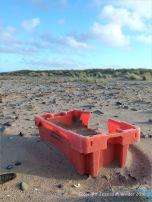 Red plastic flotsam fishing crate washed ashore