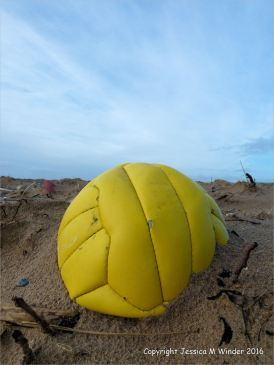 Yellow plastic football washed ashore as flotsam