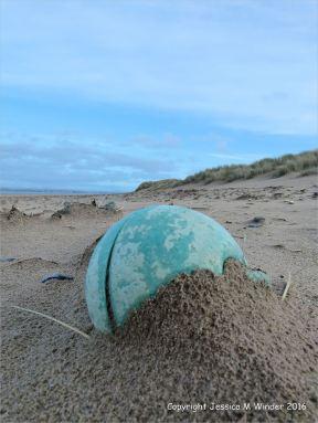 Green plastic fishing buoy washed up as flotsam