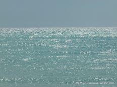 Sunlight sparkles on the sea beneath a hazy blue sky
