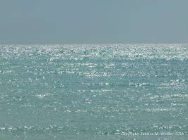 Sunlight sparkles on the sea beneath a hazy blue sky