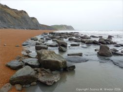 Low tide at Seatown, Dorset, England, showing boulders and horizontal beds of Belemnite Marls.