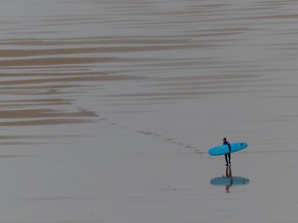 Surfer with blue board walking across wet sandy beach at low tide