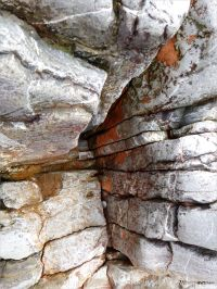 Water-worn limestone rock layers with red haematite on the Worms Head Causeway in Gower, South Wales.