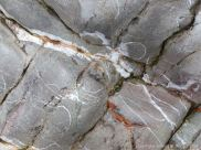 Water-worn limestone with calcite and haematite veins on the Worms Head Causeway in Gower, South Wales.
