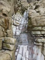Gully of water-worn limestone rock layers on the Worms Head Causeway in Gower, South Wales.