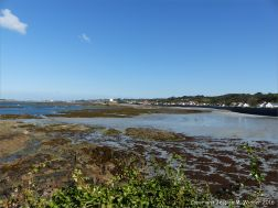 View looking over rocks towards Fort Grey at Rocquaine Bay on Guernsey