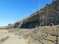 Maintainance work with scaffolding on the stone seawall at Rocquaine Bay