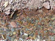 Stream across the red pebbles on the beach at Wasson Bluff