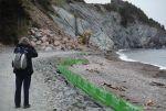 Mechanical digger moving granite boulders for coastal rip-rap sea defence at Presqu'ile