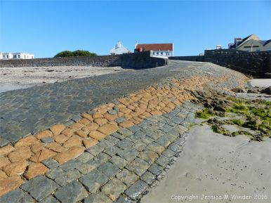 Stone slipway of contrasting colours made of dark grey Bordeaux Diorite and orange Cobo Granite at Cobo Bay