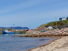 View of the harbour at White Pont in Cape Breton with rip-rap boulders of granitic pluton rock.