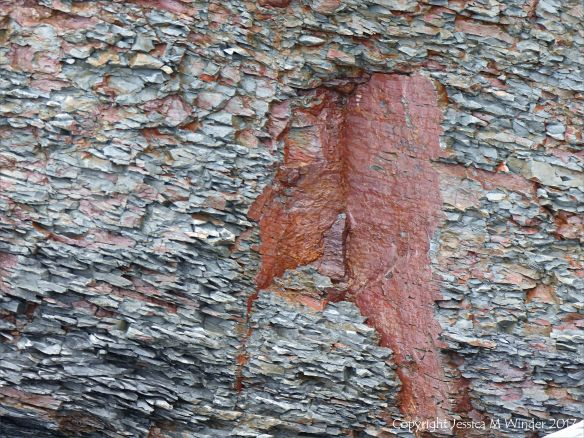 Fractured and crumbling grey rock revealing red sediments