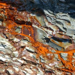 Iron-stained water running down cliff strata