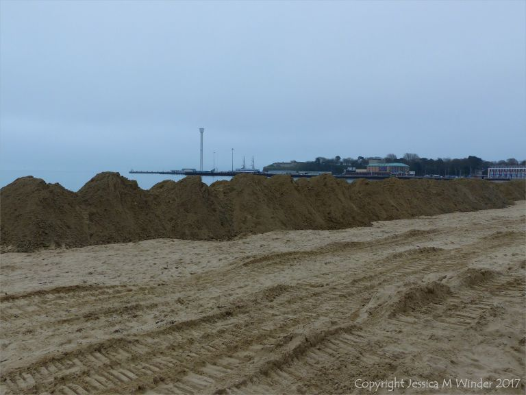 Piles of imported sand on Weymouth Beach