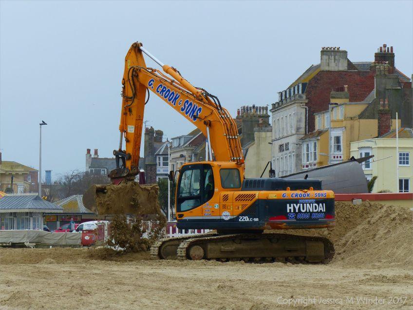 Mechanical digger moving fresh sand on Weymouth Beach
