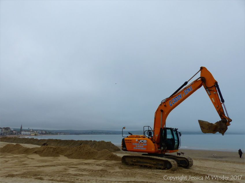 Mechanical digger moving fresh sand on Weymouth Beach