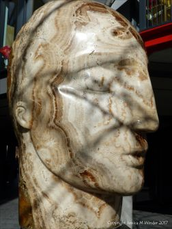 Carved stone head by Emily Young displayed at Neo Bankside in London