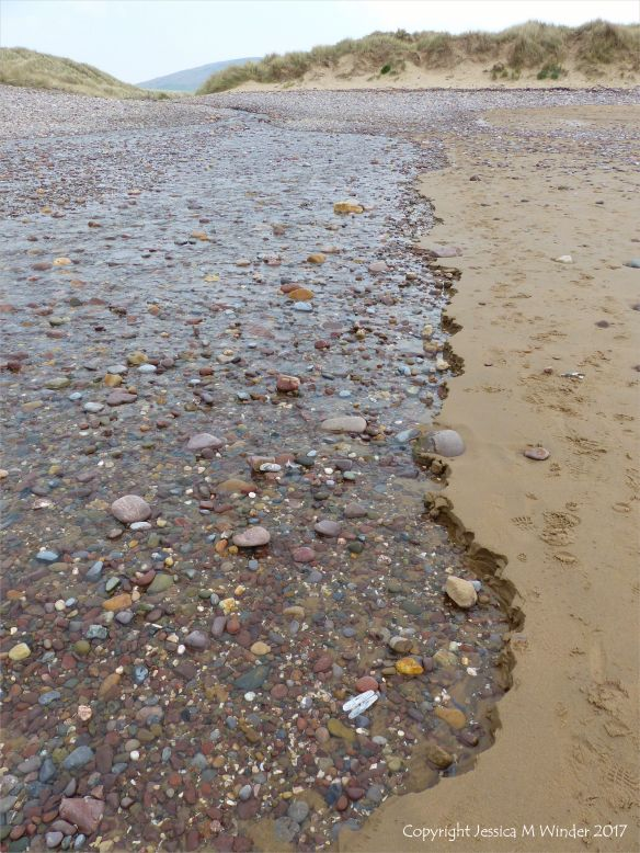 Beach stream with pebbles running through sand