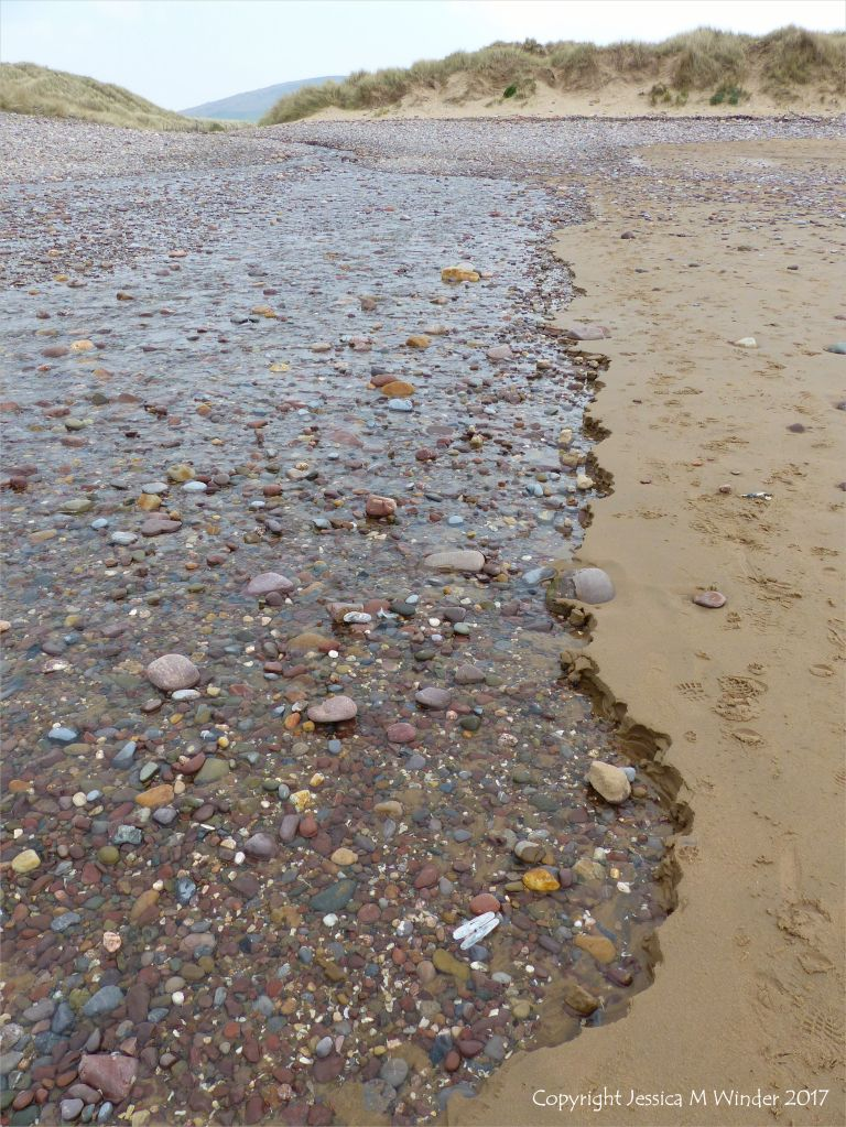 Beach stream with pebbles running through sand