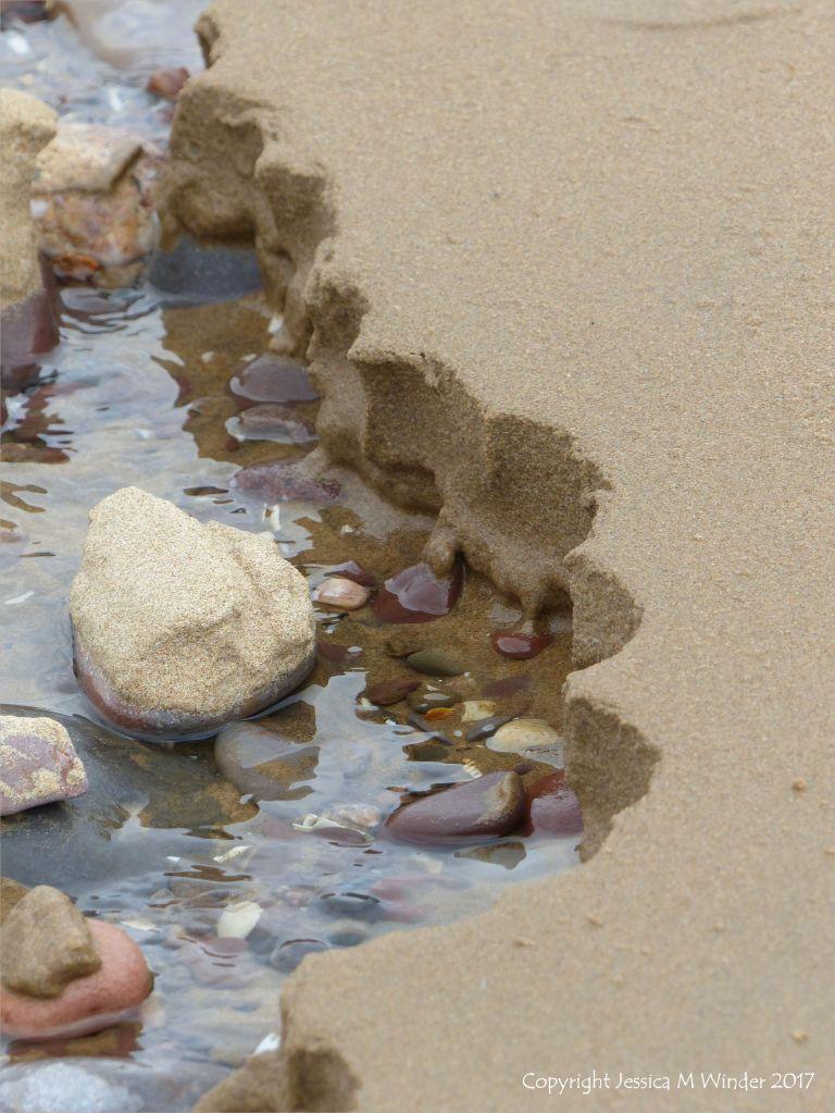 Scalloped sandy edge to a beach stream