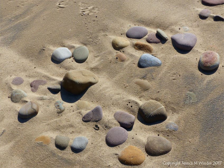 Coloured beach stones in damp sand between high and low tide levels