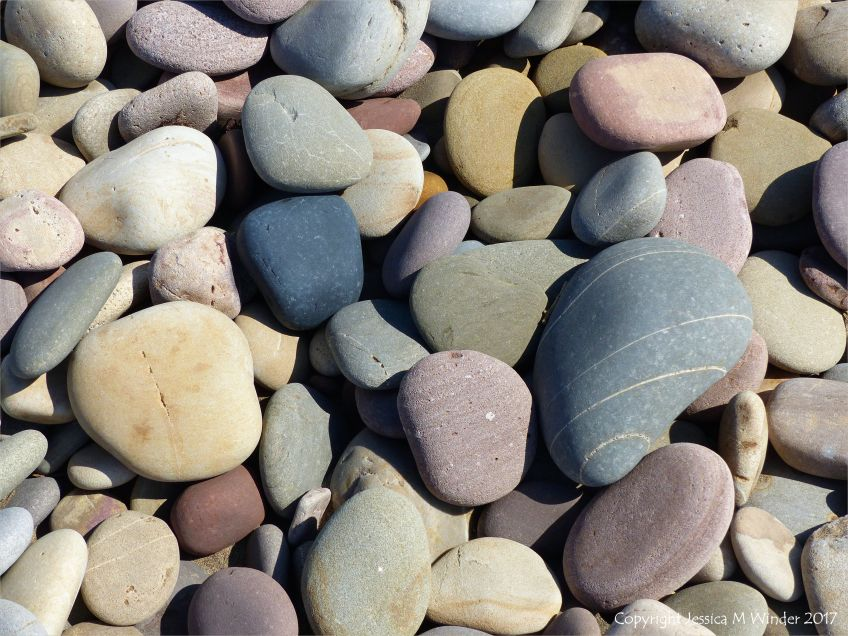 Pebbles on the seashore at Rhossili Bay in Gower, South Wales