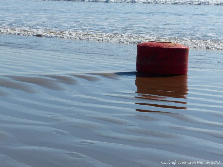 Stranded mooring buoy about to be covered by the waves again